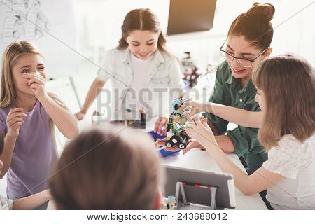 Cheerful Woman And Outgoing Children Making Robot During Lesson. Positive Education Concept