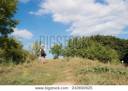 Man With Backpack Walks On Hill On Sunny Day. Hiking Concept. Traveller With Backpack Hiking In Moun
