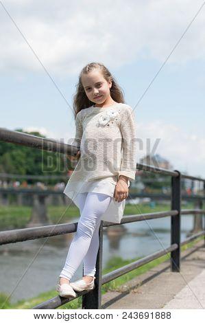 Kid girl with long hair walks near riverside, river on background. Girl child tourist enjoy sightseeing while walks. Girl or schoolgirl on vacation enjoy travelling and sightseeing. Vacation concept. poster