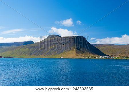 Blue Sea Water On Mountain Landscape In Isafjordur, Iceland. Hilly Coastline On Sunny Blue Sky. Summ