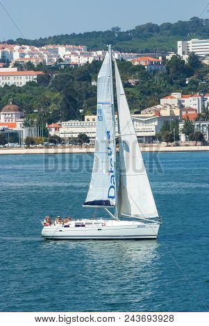 Lisbon, Portugal - April 03, 2010: Sailing Boat In Sea On Urban Landscape. Sailboat With White Sail