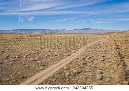 Panoramic view of rocky desert mountains above a desert road and bridge. poster