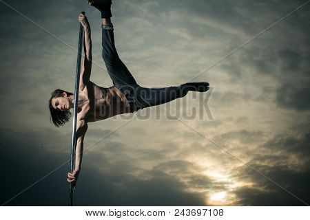 Young Muscular Man Dancing On Pylon In Sunset. Pole Dance Sport. Strong Man Dancer Workout On Pole.