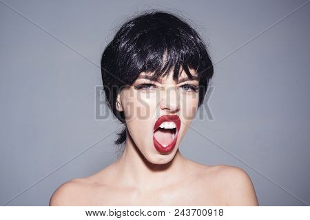 Woman Wearing Black Wig Isolated On Gray Background. Girl With Red Lips Makeup Shouting, Madness Con