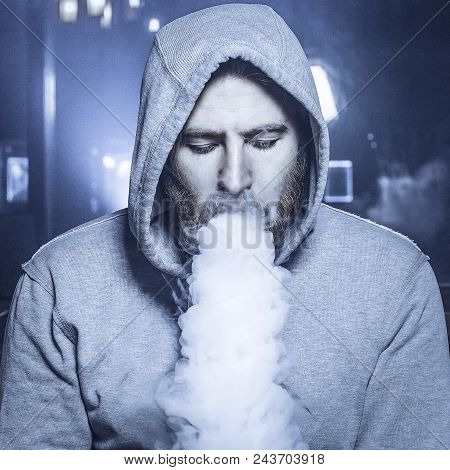 Punk Hipster Man With Beard In The Vape Shop Is Sitting At The Bar And Smoking A Mechanical Vape Dev
