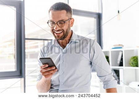 Image closeup of smiling employer guy in white shirt standing in office room near big window and using smartphone for work