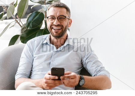 Image of smiling employer guy in white shirt sitting in office armchair near green plant and using smartphone for work