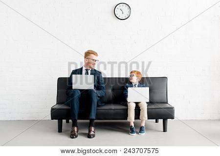 Smiling Father And Son Businessmen In Eyeglasses Using Laptops And Looking At Each Other