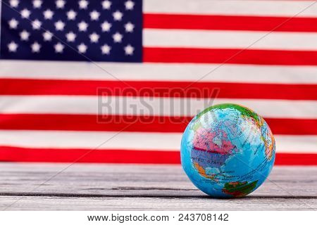 Globe On American Flag Background. Globe On Wooden Table With Usa Flag In The Background. Education