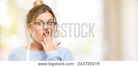 Young woman shop owner, wearing apron covers mouth in shock, looks shy, expressing silence and mistake concepts, scared