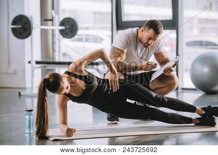 Male Personal Trainer Looking At Timer And Young Athletic Woman Doing Side Plank On Fitness Mat