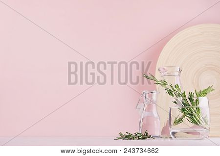 Green Rosemary Twigs In Transparent Glass Vase And Beige Bamboo Plate On Soft Pink Pastel Background