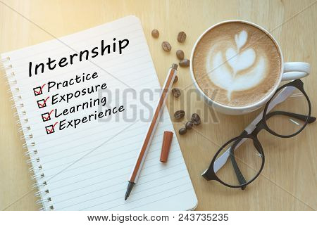 Concept Internship Benefits Message On Notebook With Glasses, Pencil And Coffee Cup On Wooden Table.