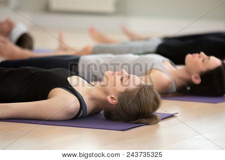 Group Of Young Yogi People Practicing Yoga Lesson, Doing Savasana Pose, Corpse Exercise, Dead Body,