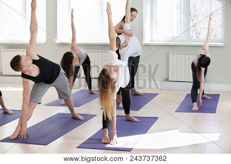 Young Female Yoga Instructor Teaching Utthita Trikonasana Pose, Extended Triangle Exercise For A Gro