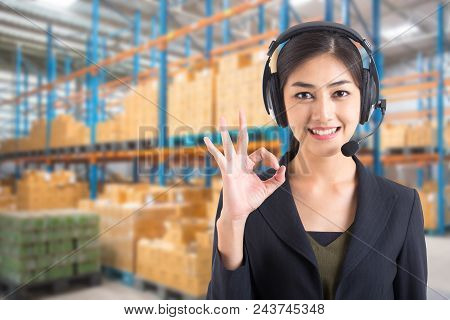 Asian Call Center Smiling At Warehouse Background.