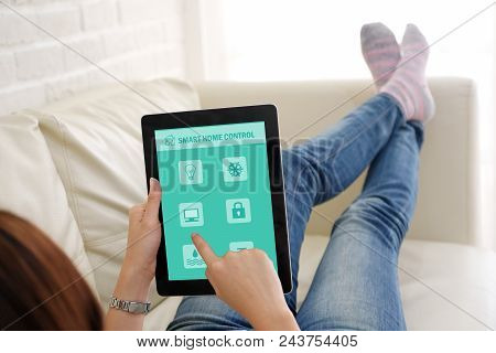 Woman Using Tablet With Smart Home Control Icon On Screen While Sitting On Sofa At Home, Smart Home
