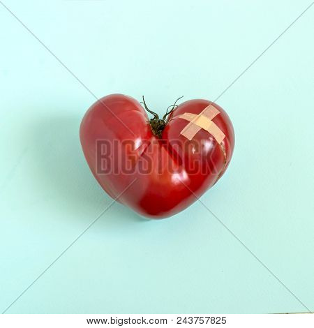 Big Tomato In Shape Of Wounded Heart With Adhesive Plaster On Blue Pastel Background. Minimal Style.