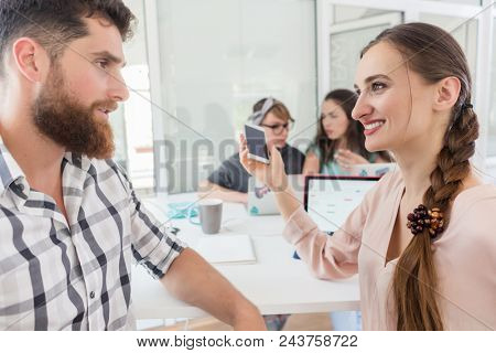 Side view of a creative female freelancer smiling to her co-worker, while making a call on the mobile phone at a shared desk in a relaxed work environment