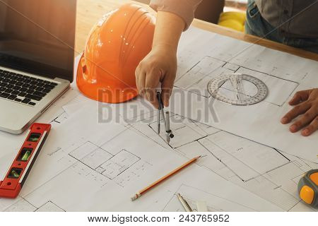 An Architect Or Engineer Working On Blueprint, An Architect Or Engineer Uses A Divider Gauge On The