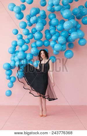 Excited Girl In Cute Black Dress Dancing With Smile On Pink Background Decorated With Blue Balls Han