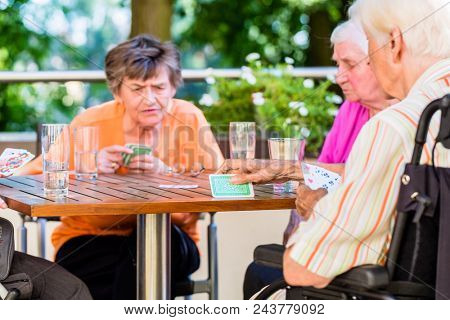 Group of seniors playing board game on terrace of retirement or nursing home