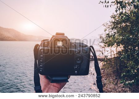 Hand Holding Camera Dslr To Travel At River Sunset,holiday Travel Vintage