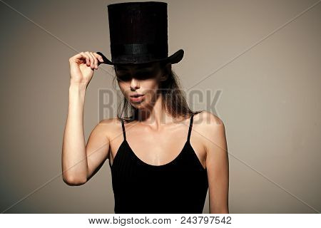 Circus. Girl In Black Fashionable Swimsuit And Hat. Fashion Model Pose In Studio On Grey Background.