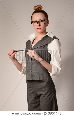 Slim Serious Young Woman Teacher In Suit Bends Pointer In Hands.