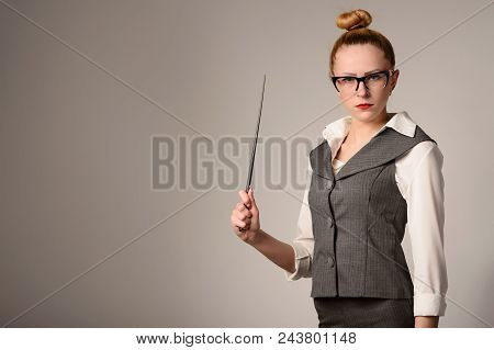 Portrait Of Young Teacher Holding Pointer. Slim Girl In A Suit Near The White Wall