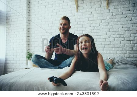 Happy Single Father And Teen Daughter With Joysticks Playing Video Game. Family Leisure Concept. Fat