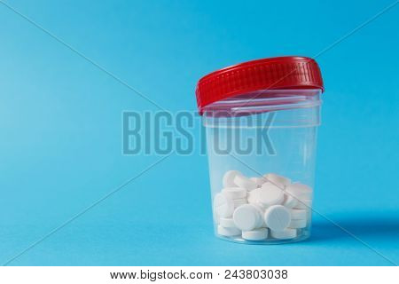 Medication Jar With White Round Tablets Arranged Abstract On Blue Color Background. Aspirin Bottle D