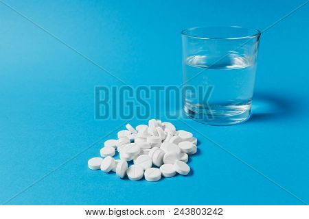 Medication Pile White Round Tablets Arranged Abstract On Blue Color Background. Aspirin, Glass Water