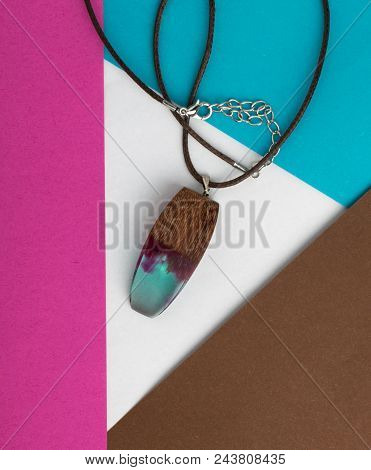Hand Made Wood Pendant On Abstract Multicolored Geometric Background. Bijouterie Made Of Epoxy Resin
