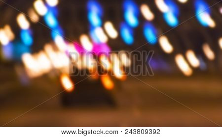 Night City View In Blur. City Street Blurry Photo. Street Life Bokeh Image. Street View With Pedestr
