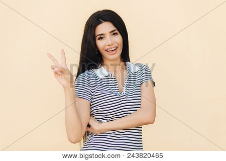 Portrait Of Cheerful Brunette Female With Joyful Expression, Makes Peace Sign With Two Fingers, Dres