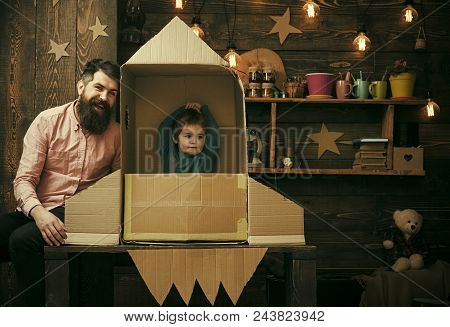 Child Dreams. Rocket Launch Concept. Kid Happy Sit In Cardboard Hand Made Rocket. Boy Play With Dad,