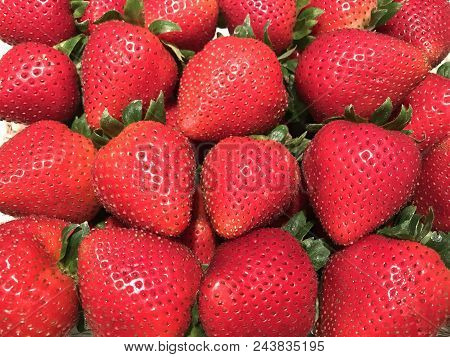 A Background Image Of Red Delicious Strawberries Packed Closely Together.