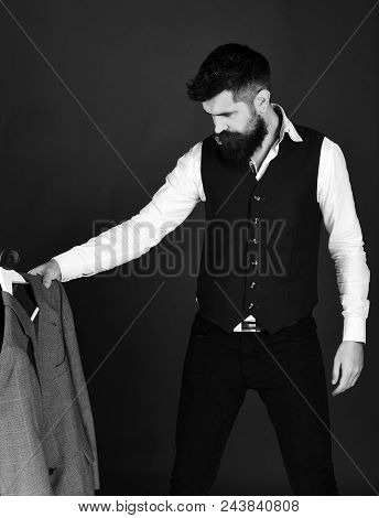Tailor At Work. Tailoring And Design Concept. Tailor With Serious Face Holds Grey Suit Or Custom Jac