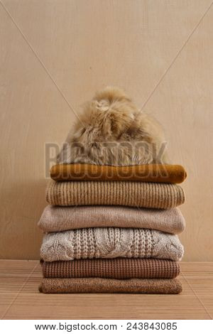 Hat on Stack of knitted sweaters-wooden background