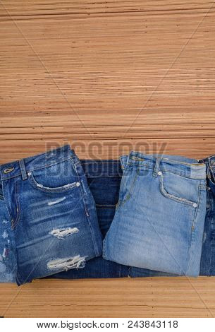 Set of jeans trouser on wooden background