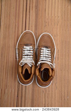 Man's brown shoes-wooden background