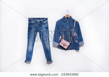 blue Embroidered flowers, jacket jeans with handbag and jeans on white background