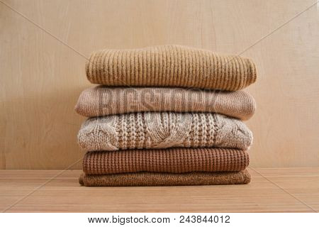 Stack of knitted sweaters-wooden background