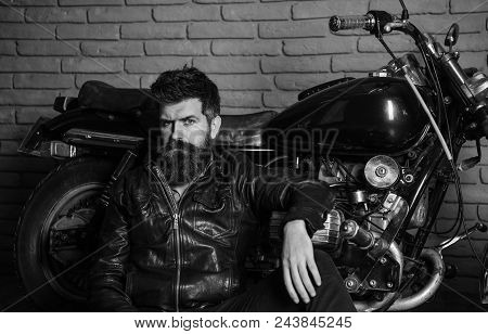 Hipster, Brutal Biker On Pensive Face In Leather Jacket Sits, Leans On Motorcycle. Bikers Lifestyle