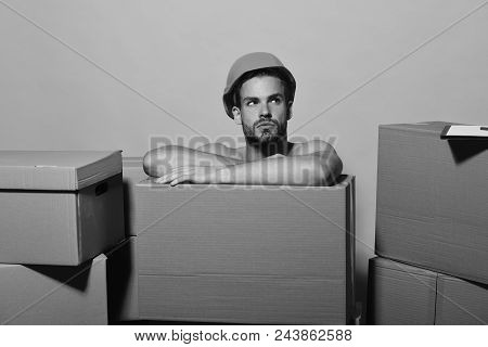 Delivery And Moving Concept. Guy With Bare Hands Hides Behind Boxes. Man With Beard Sits Yellow Back