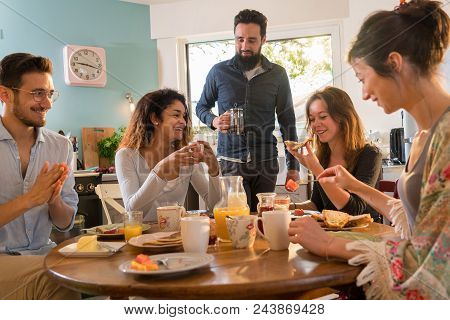 A Group Of Multi-ethnic Friends Gathered Around A Table In The Kitchen For Breakfast. In A Warm And