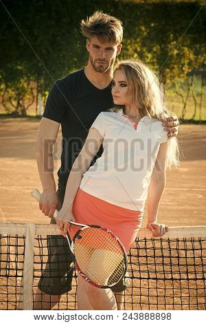 Sporty Couple. Relationship, Relations, Family. Couple In Love Stand At Tennis Net On Clay Court. Sp