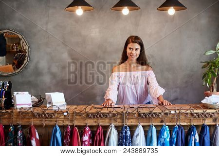 Portrait Of Female Store Owner Standing Behind Cash Desk