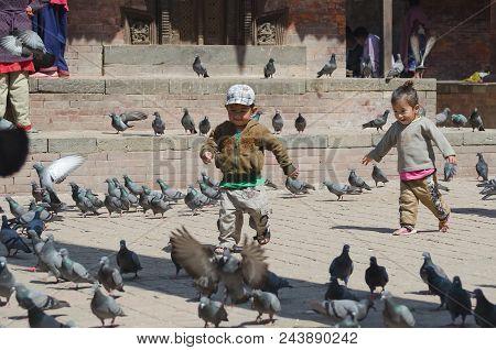 Kathmandu, Nepal, 2013-02-26: Little Kids Startles Numerous Pigeons At The Ancient Square